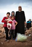 Syrian refugee family. Atmeh, Idlib province,Syria. A woman and her five daughters stand in the Atmeh refugee camp with a plastic bag containing the few