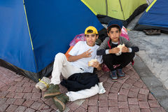 Syrian refugees in Greece. Two unidentified boys from Syria eat a sandwich outside their tent on October 14, 2015 in Kos island, Greece. Thousands of Syrian Stock Photography