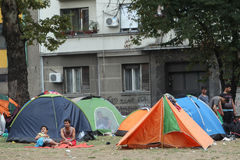 Syrian refugees in Serbia. BELGRADE, SERBIA - SEPTEMBER 5 : Syrian refugees resting in a park in tents near the train station and waiting for the transport to Stock Photography