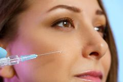 Syringe for beauty injection on the background of the face of a girl close-up, isolated on blue background
