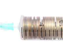 Syringe with coins concept financial investments Stock Image