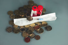 Syringe and Coins Stock Images