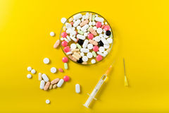 Syringe and colorful pill and capsules on background. Top view Royalty Free Stock Image
