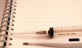 A syringe, a digital thermometer on a notebook. Copy space. Free space for text Stock Images