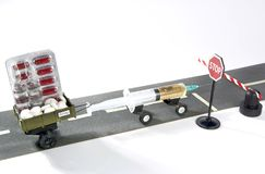 Syringe with doping is riding on the road with trailer full of pills, but can not cross the stop sign and a barrier. Syringe with doping vaccine is riding on Royalty Free Stock Image