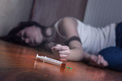Syringe with drugs. Close-up on the floor of the syringe with the drug. In the background, a young drug addict Stock Photo