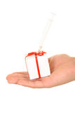 Syringe in gift on palm. On white background Stock Photos