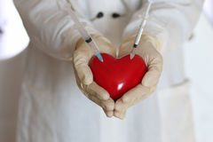 Syringe in heart doctor hand Stock Images