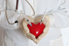 Syringe in heart doctor hand Royalty Free Stock Image
