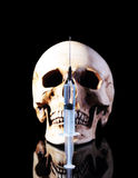 Syringe and human skull Stock Images