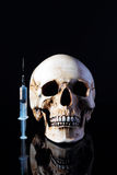 Syringe and human skull Stock Photo