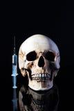 Syringe and human skull Stock Photo