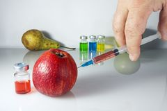 Nitrates and Green Apple. The syringe injects nitrates into the apple Royalty Free Stock Photos