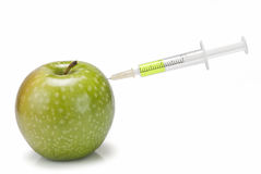 Syringe inserted in  an apple. Royalty Free Stock Photo