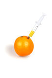 Syringe inserted into an orange Stock Photo