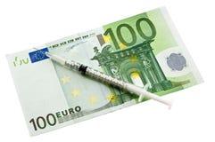Syringe lying upon european currency Stock Photo