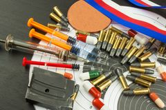 Syringe and medals. Doping in shooting sport. Abuse of anabolic steroids for sports. Deception in biathlon. Stock Image