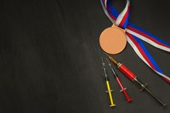 Syringe and medals. Doping in sport. Abuse of anabolic steroids for sports. Anabolic steroids spilled on a wooden table. Stock Photos
