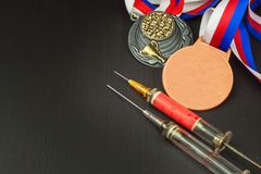 Syringe and medals. Doping in sport. Abuse of anabolic steroids for sports. Anabolic steroids spilled on a wooden table. Royalty Free Stock Image
