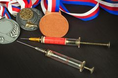 Syringe and medals. Doping in sport. Abuse of anabolic steroids for sports. Anabolic steroids spilled on a wooden table. Stock Photo