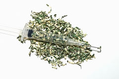 Syringe with Money. Shredded money with a syringe full.  Concept or metaphor for cost of drugs, health, wasting money on drugs, medical plans, etc Royalty Free Stock Image