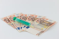 Syringe on money bills Stock Images