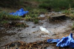 Syringe and the needle in the mud on the ground stock photo