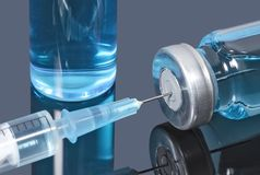 Syringe with a needle stuck in a vial of blue vaccine on dark background. The medical needle speared into the vial with blue liquid stock image