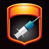 Syringe in orange display. Orange display with black halftone background of syringe Royalty Free Stock Photos