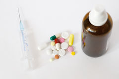 Syringe, pills and brown vial Stock Photos
