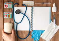 Syringe, stethoscope, blank page notepad, bandage, pill, elastic bandage and gloves on the doctor table. Medical diagnosis or stock photography