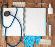 Syringe, stethoscope, blank page notepad, bandage, pill and gloves on the doctor table. Medical diagnosis or doctor prescription stock photos