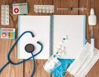 Syringe, stethoscope, blank page notepad, bandage, pill and gloves on the doctor table. Medical diagnosis or doctor prescription royalty free stock photos