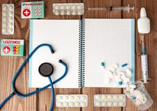Syringe, stethoscope, blank page notepad, bandage, pill and gloves on the doctor table. Medical diagnosis or doctor prescription royalty free stock photography