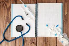Syringe, Stethoscope, blank page notepad and pill on the doctor table. Medical diagnosis or doctor prescription mockup royalty free stock photos
