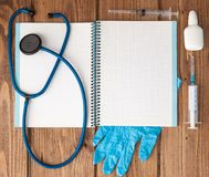 Syringe, stethoscope, blank page notepad, pill and gloves on the doctor table. Medical diagnosis or doctor prescription mockup.  stock images