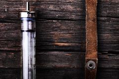 Syringe and suede tourniquet on the rough wooden surface as a co. Ncept of drug addiction Stock Photo