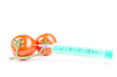 Syringe and tomatoes Royalty Free Stock Photos