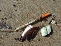 Syringe  washed up on sandy beach shore Stock Photo