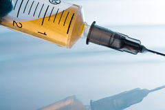 Syringe with yellow liquid Stock Photography