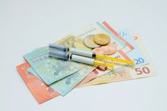 Syringes and bank notes Royalty Free Stock Images