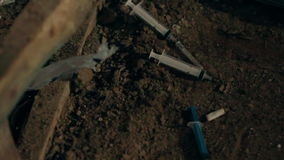 Syringes from drug addicts in the mud stock footage