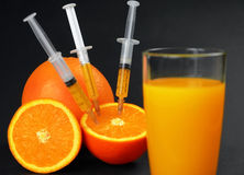 Syringes injected into orange and juice Royalty Free Stock Image