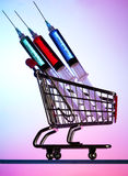 Syringes and a miniature shopping cart Royalty Free Stock Image