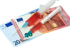 Syringes with the needle with medicine and euros. On white background Royalty Free Stock Image
