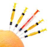 Syringes and orange. Syringes and orange on white background royalty free stock photo