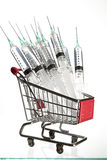 Syringes in a shopping cart Royalty Free Stock Photos