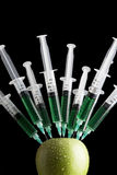 Syringes stuck in an apple Royalty Free Stock Images