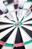 Syringes stuck in a dartboard Royalty Free Stock Photography