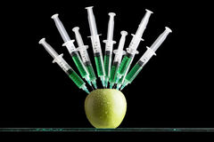 Syringes Stuck In An Apple Stock Image